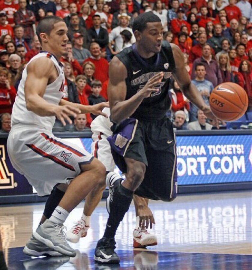 Washington's C.J. Wilcox (23) and Arizona's Nick Johnson, left, look for a loose ball during the first half of an NCAA college basketball game at McKale Center in Tucson, Ariz., Wednesday, Feb. 20, 2013. (AP Photo/Wily Low)