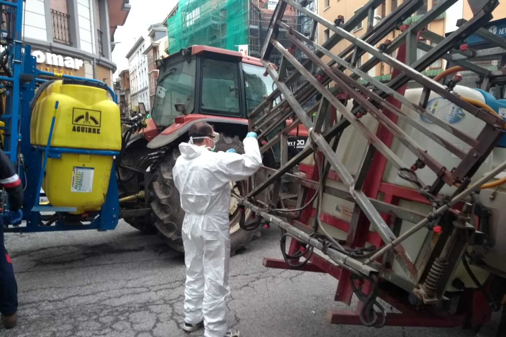 On the front line of the coronavirus threat in Spain, tractors scatter the streets with hope