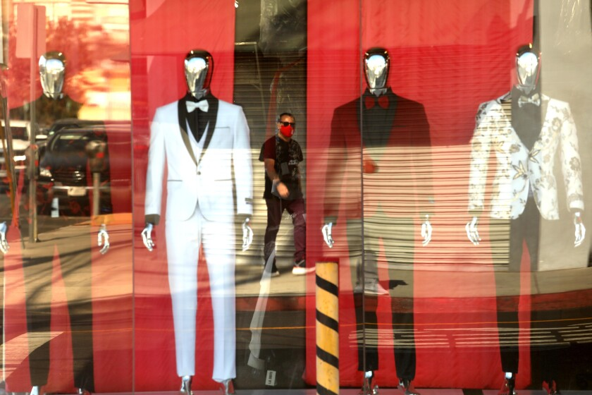 A pedestrian, wearing a mask, is reflected in the storefront of L.A. Suits along Maple Street in the Garment District.