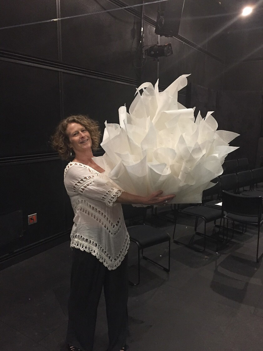 Choreographer Yolande Snaith with one of the fanciful pieces of headgear she designed and made for 'Measuring the Dream,' first of this season's IDEAS performance series at UC San Diego.