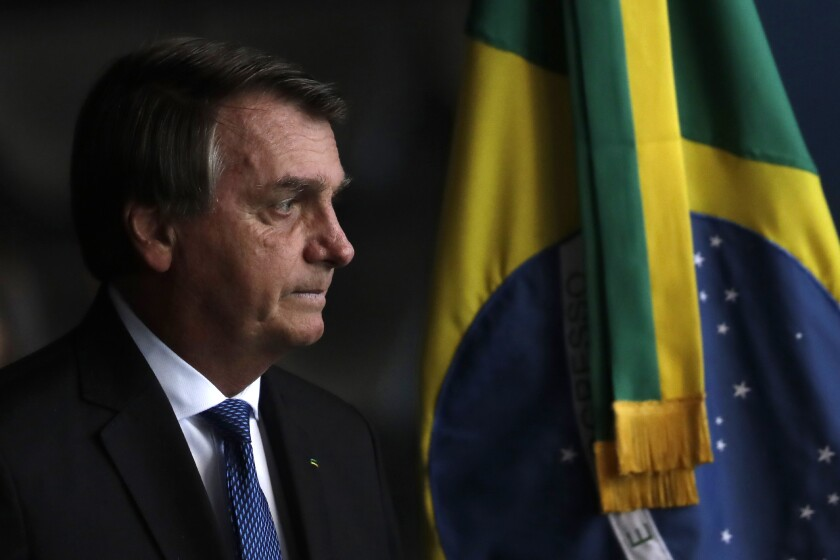Brazil's President Jair Bolsonaro arrives to the Ministry of Justice to attend the inauguration of the new public defender, in Brasilia, Brazil, Tuesday, Jan. 19, 2021. (AP Photo/Eraldo Peres)