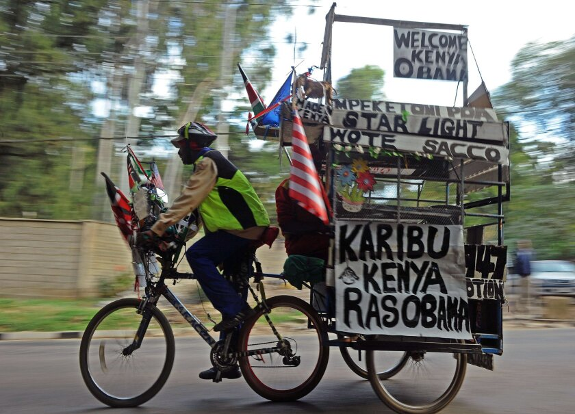 An man on a bicycle pulls a trailer with messages welcoming President Obama to Kenya in Nairobi on Thursday.