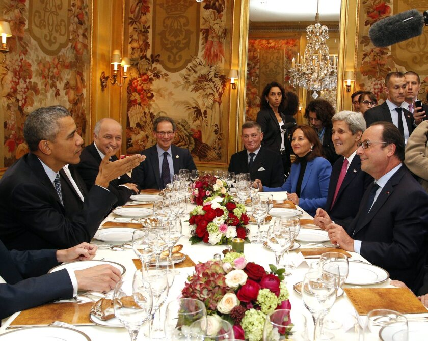 President Obama sits with French President Francois Hollande (right), Secretary of State John Kerry, and other officials as they have dinner at the Ambroisie restaurant in Paris on Nov. 30.