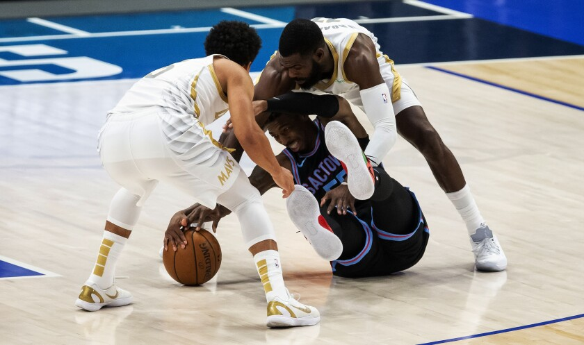Sacramento Kings guard Delon Wright, center, battles Dallas Mavericks guard Jalen Brunson, left, and forward Tim Hardaway Jr. (11) for a loose ball during the half of a NBA basketball game, Sunday, April 18, 2021, in Dallas. (AP Photo/Brandon Wade)