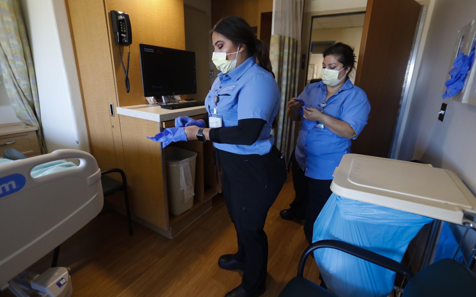 Debbie Gastelum y Karla Velarde se pusieron guantes antes de desmontar y desinfectar a fondo la habitación de un paciente en el Hospital Scripps Mercy de San Diego.