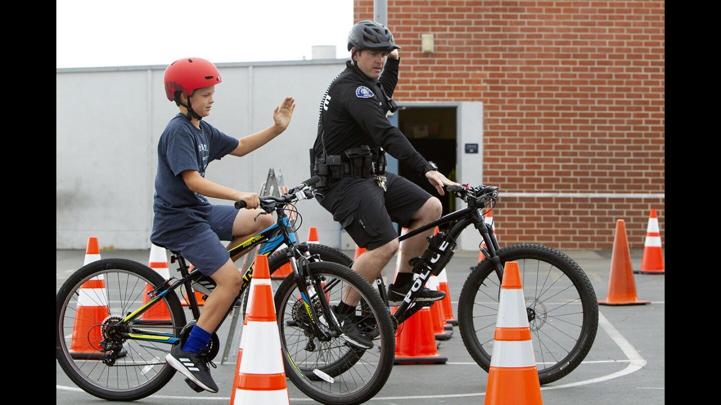 Fourth-grader George Bielen makes a right-turn hand signal as Costa Mesa police Officer Trevor Jones guides him through an obstacle course during Wednesday's Bike Rodeo at Kaiser Elementary School in Costa Mesa.