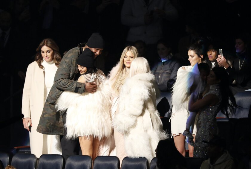 "Lamar Odom, second left, hugs Kylie Jenner as Caitlyn Jenner, left, Khloe Kardashian Odom, center, Kim Kardashian, Kendall Jenner, North West and Kourtney Kardashian (both out of spotlight) attend the unveiling of the Yeezy collection and album release for Kanye West's latest album, ""The Life of Pa"