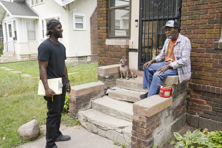 Organizer Latrell Snider, left, talks with Minneapolis resident Steven Black on July 22, 2021, ahead of the November election, as small armies of door-knockers are hitting the Minneapolis streets seeking to build support for a ballot question that would eliminate the city's police department and replace it with something new. It's the second such attempt by activists and some elected officials since George Floyd died at the hands of city police after last year's effort didn't make the ballot. (AP Photo/Jim Mone)