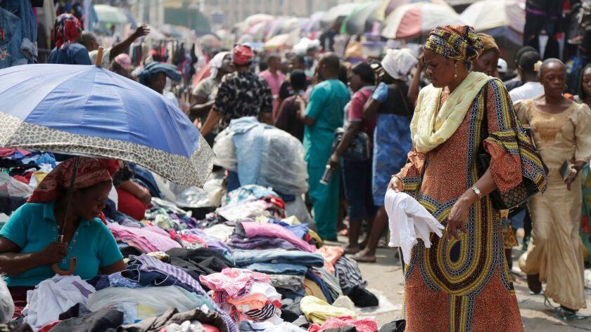 Pedestrians shop in a roadside market in Lagos, Nigeria, Friday, Jan. 12, 2018. Africans were shocke