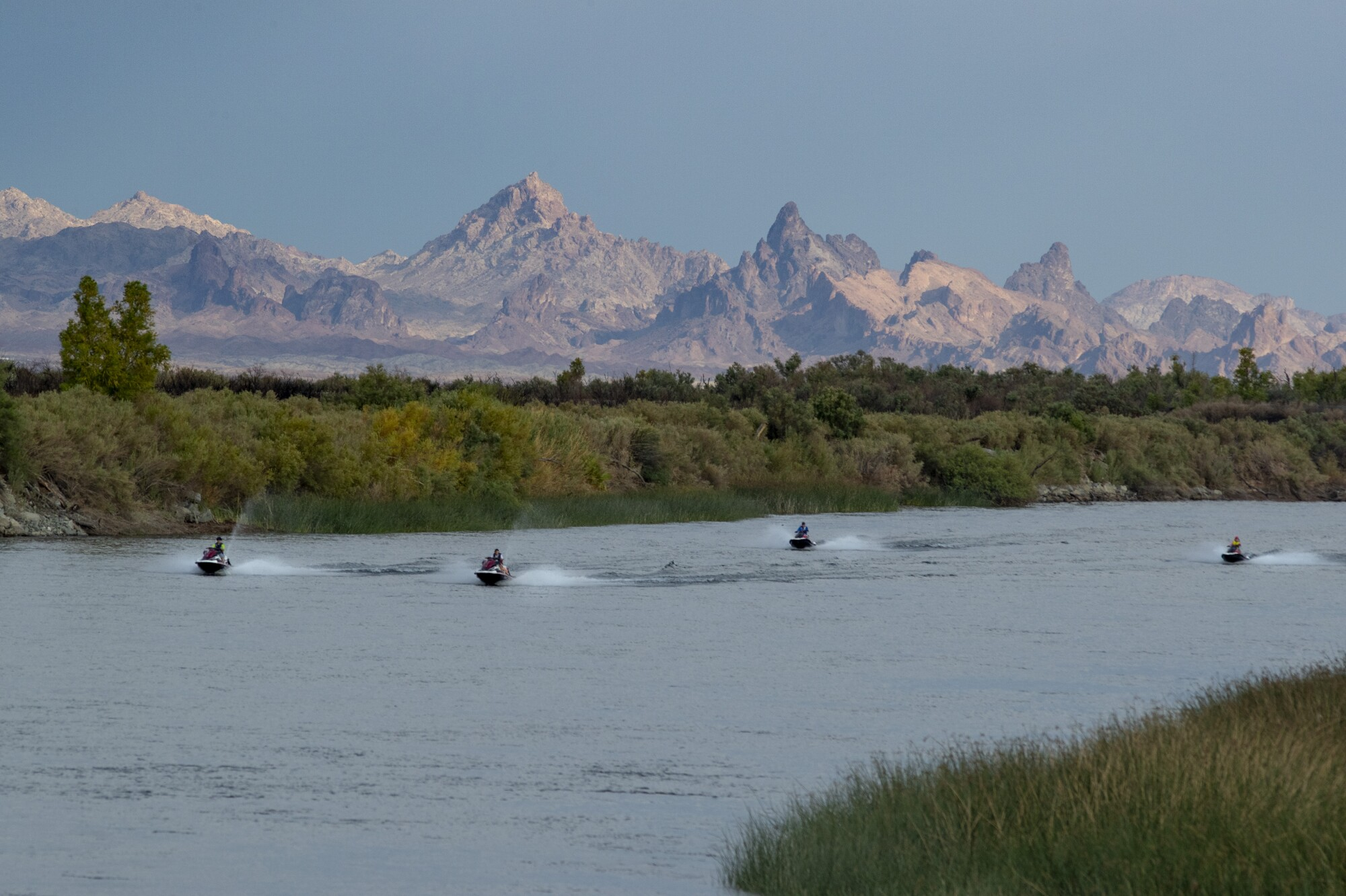 Jet skiers power up the Colorado River against a backdrop of The Needles