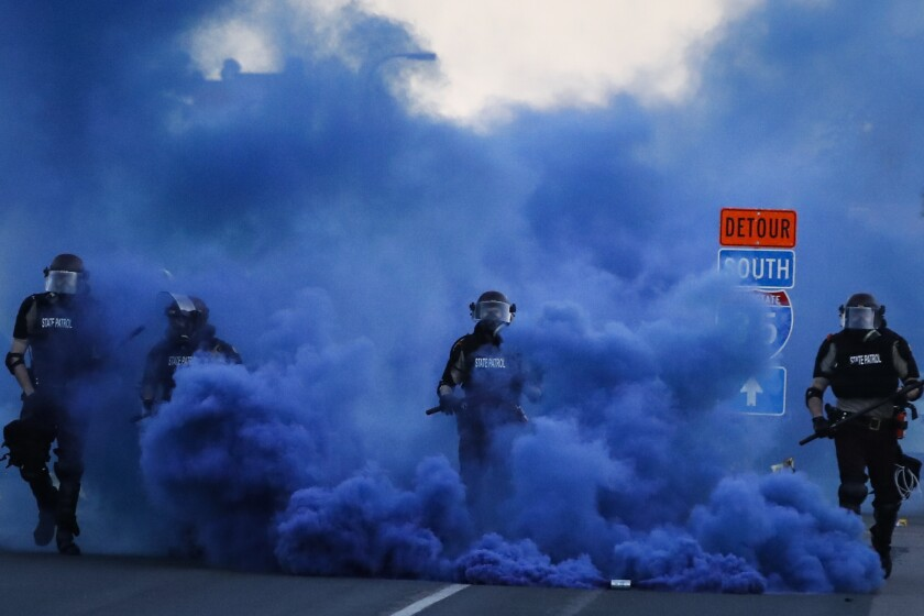 Police in riot gear walk through a cloud of blue smoke