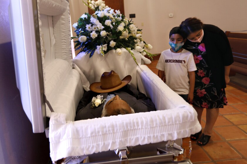 A mother and son pay respects to Fernando Aguirre, who died of COVID-19 at age 69.