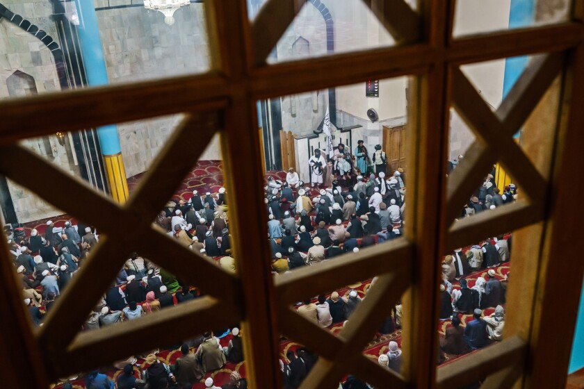 A view from a window above of a mosque crowded with men