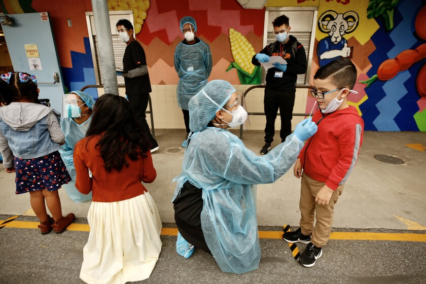 A child is tested for a coronavirus infection at Heliotrope Avenue Elementary School.