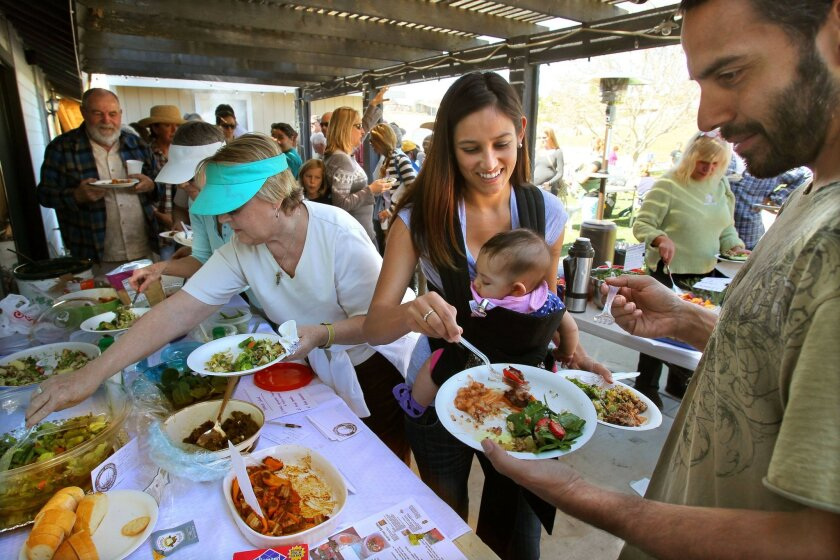 Emily and Tyson Perez enjoy the potluck lunch Saturday at Primal Pasturs with their daughter Cambria.