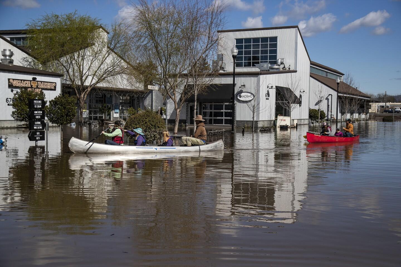 Algunas personas se transportan en canoas en las inundaciones que rodean el mercado de Barlow en Sebastopol, California.