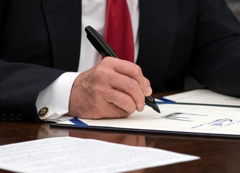 El presidente estadounidense, Donald J. Trump, firma un proyecto de ley bipartidista para detener el flujo de opiáceos en los Estados Unidos hoy, miércoles 10 de enero de 2018, en la Oficina Oval de la Casa Blanca, en Washington, DC (EE.UU.). EFE