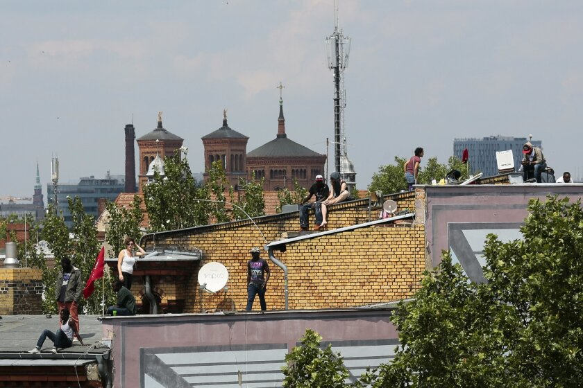 Refugees and supporters  on the roof of the occupied Gerhart Hauptmann School in Berlin, Germany, Friday, June 27, 2014. A group of refugees from different countries have been on the roof of the school for three days  to protest against the eviction from the school by police and their possible depo