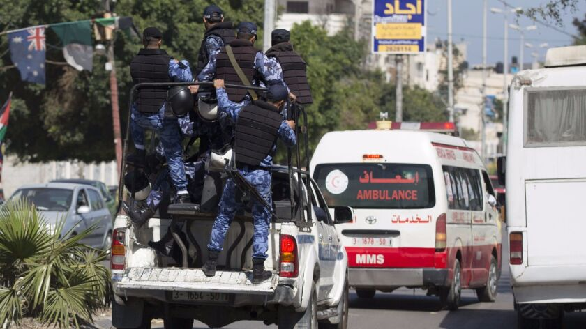 Hamas police secure the area as an ambulance reportedly carrying the bodies of men accused of collaborating with Israel leaves the main police building in Gaza City on Thursday.