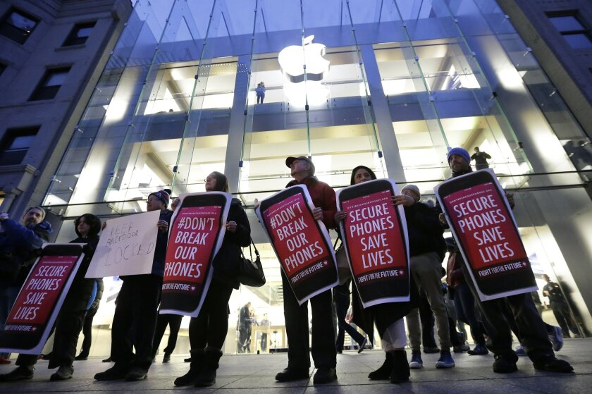 Protesters carry placards outside an Apple store Tuesday, Feb. 23, 2016, in Boston. Demonstrators are expected to gather in a number of cities Tuesday to protest the FBI obtaining a court order that requires Apple to make it easier to unlock an encrypted iPhone used by a gunman in December's shooting in San Bernardino, Calif. (AP Photo/Steven Senne)