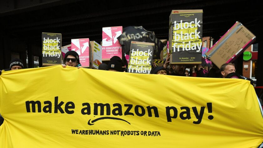 Demonstrators hold a banner and posters during a rally against the online retailer Amazon in Berlin,