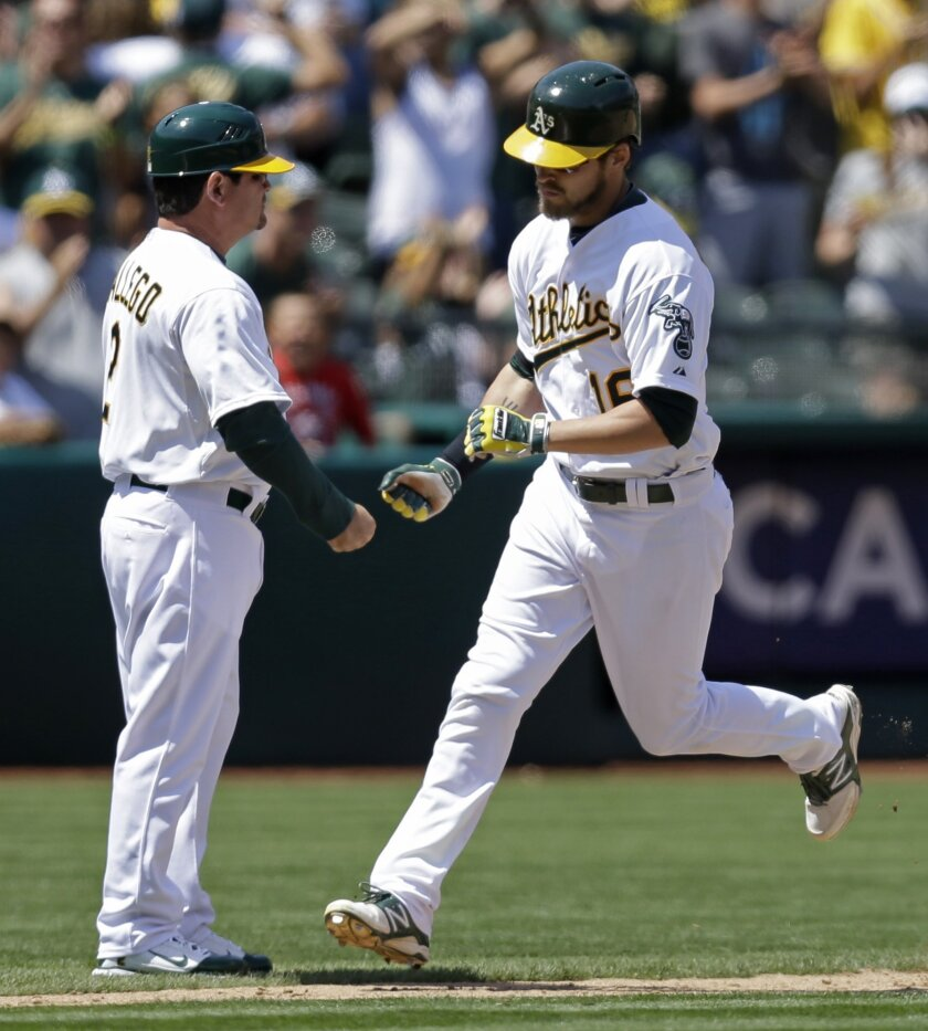 Oakland Athletics' Josh Reddick, right, is congratulated by third base coach Mike Gallego after Reddick hit a home run off Kansas City Royals' James Shields in the sixth inning of a baseball game Sunday, Aug. 3, 2014, in Oakland, Calif. (AP Photo/Ben Margot)