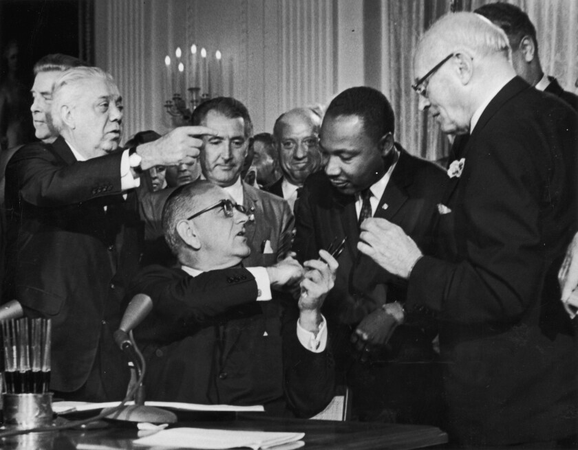 President Lyndon B. Johnson shakes the hand of Dr. Martin Luther King Jr. at the signing of the Civil Rights Act while officials look on.