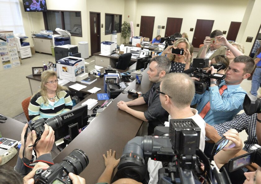 Surrounded by the media, David Moore, center in dark shirt, and his partner David Ermold attempt to apply for a marriage license at the Rowan County Courthouse in Morehead, Ky., on Sept. 1, 2015. They were turned away.