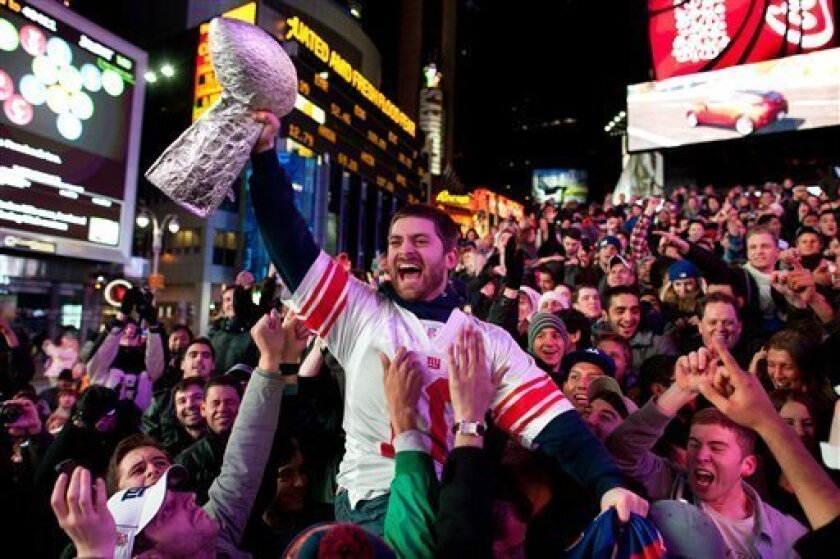 Tom Amendola, of Secaucus, N.J., celebrates a New York Giants win against the New England Patriots in the NFL football Super Bowl with a homemade trophy in Times Square, Sunday, Feb. 5, 2012, in New York. (AP Photo/John Minchillo)