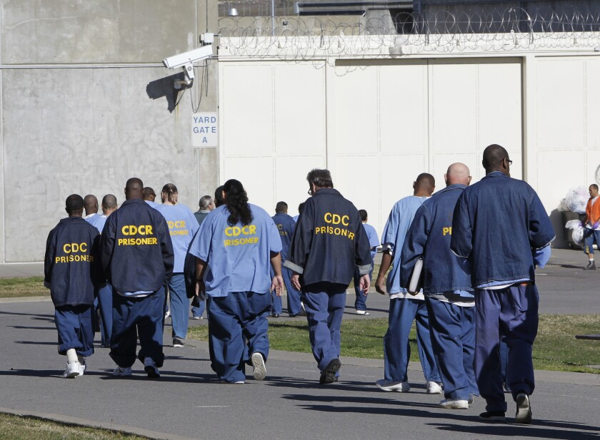 FILE - In this Feb. 26, 2013, file photo, inmates walk through the exercise yard at California State Prison Sacramento, near Folsom, Calif. Racial disparities have narrowed across the United States criminal justice system since 2000, though blacks remain significantly more likely to be impacted than whites, according to a study released Tuesday, Dec. 3, 2019, by the nonpartisan Council on Criminal Justice. (AP Photo/Rich Pedroncelli, File)