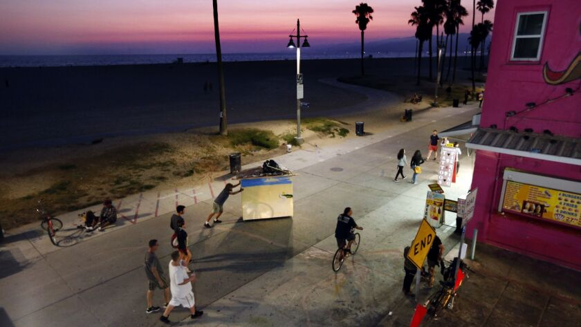 A homeless man wheels his portable, small home, which has a bed inside, along the boardwalk in Venice Beach in 2016.