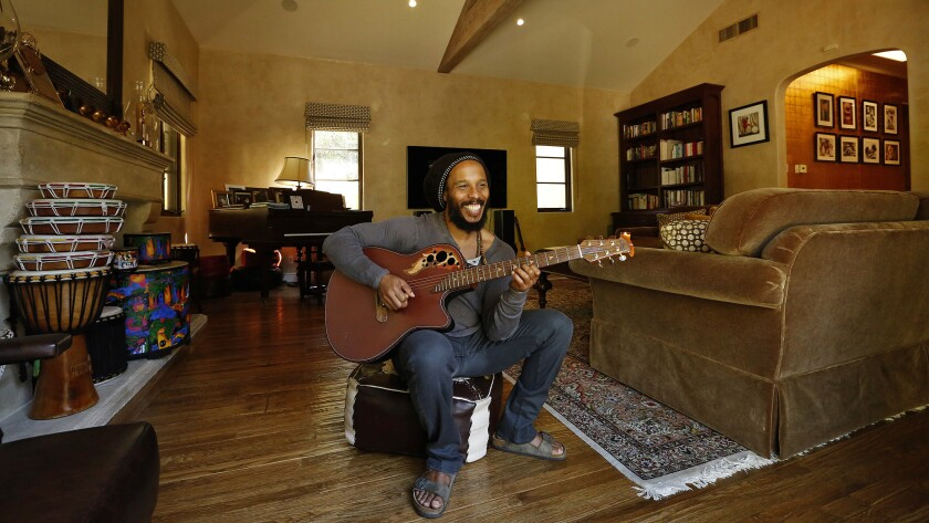 """In his library/TV room, Marley says, """"my daughter will play the piano, and we jam and make music. We love to watch movies as a family and have a big screen TV."""""""