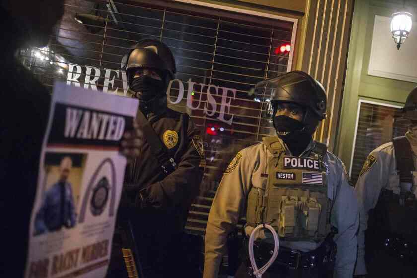 Protesters holding an image of officer Darren Wilson walk past police guarding a business in Ferguson, Missouri, November 29, 2014.