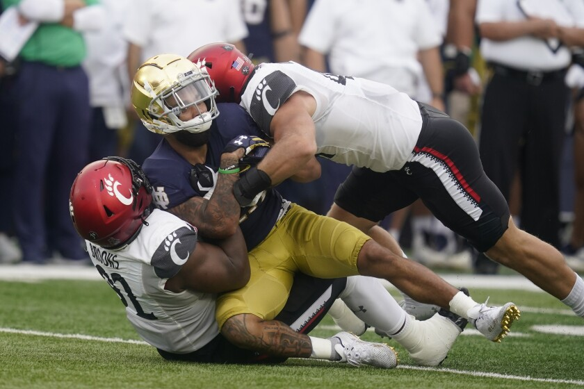 Notre Dame's Kyren Williams (23) is tackled by Cincinnati's Curtis Brooks (92) and Joel Dublanko (41) during the first half of an NCAA college football game, Saturday, Oct. 2, 2021, in South Bend, Ind. (AP Photo/Darron Cummings)