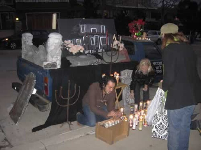 La Jollans light candles and share memories in front of a makeshift, mobile altar to Irving Gill's demolished Windemere cottage Jan. 27. Pat Sherman
