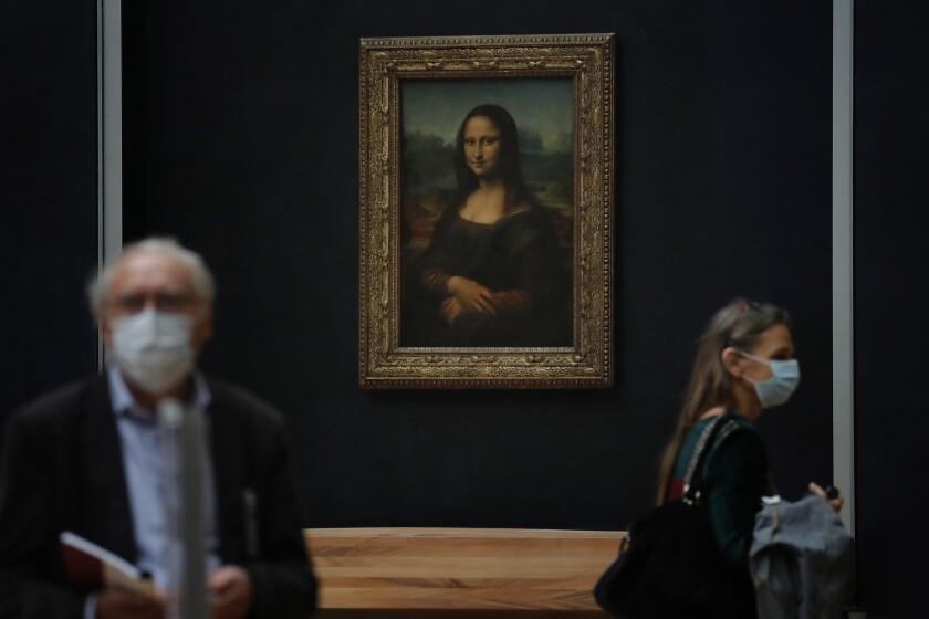 Periodistas pasan frente a la Mona Lisa de Leonardo da Vinci