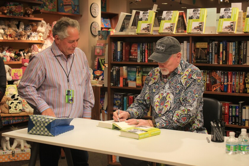 """Mike Love signs a copy of """"Good Vibration, My life as a Beach Boy."""""""