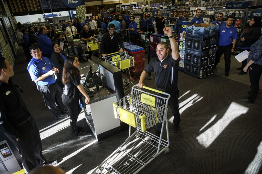 Geek Squad employee Daniel James pushes a cart while pretending to be a customer exiting the store with a purchase. It's part of the Black Friday preparations at the Best Buy in Atwater Village.