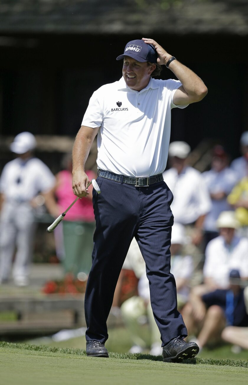 Phil Mickelson reacts to a missed putt on the ninth green during the final round of the Memorial golf tournament on Sunday, June 1, 2014, in Dublin, Ohio. (AP Photo/Darron Cummings)