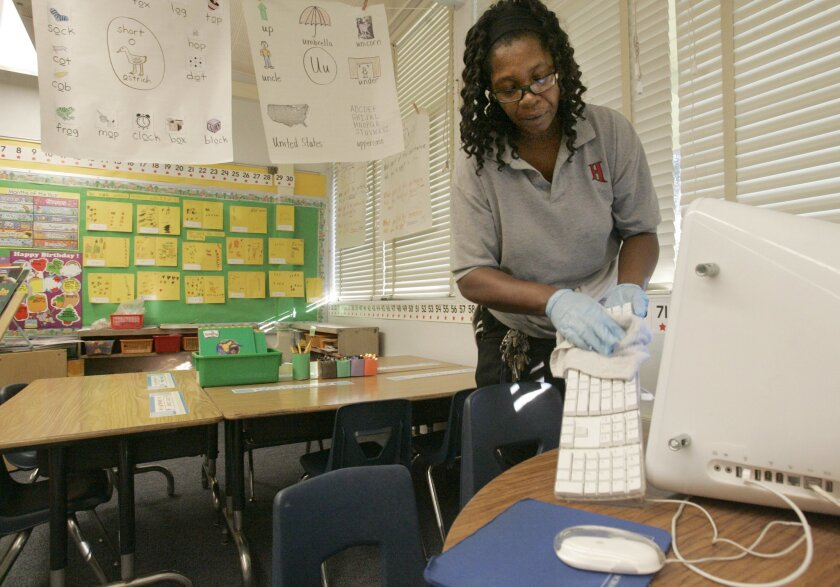 Sheila Morris, custodian at Ross Elementary in San Diego, makes sure surfaces children might touch are cleaned with bleach.