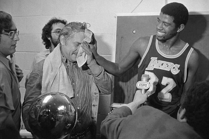 Magic Johnson wipes the face of Lakers owner Jerry Buss after he poured champagne on him following the Lakers' 1980 NBA championship victory over the 76ers.