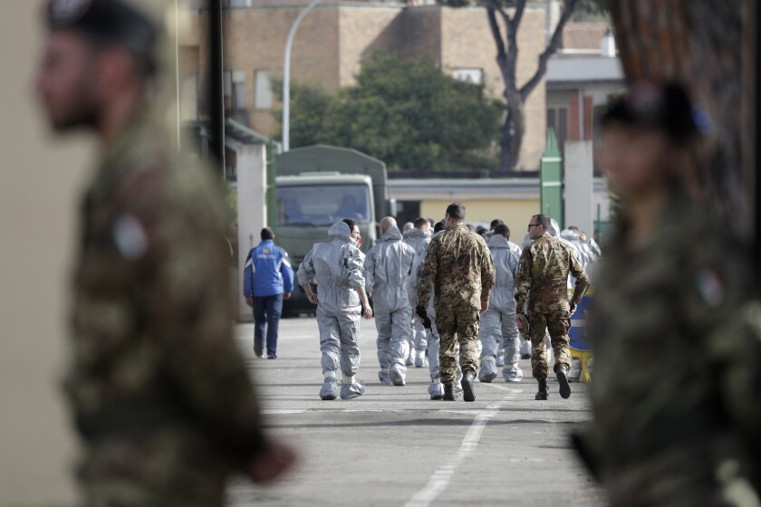 People wearing protective suits and military personnel walk inside a military complex where 56 Italians evacuated from Wuhan, China, will be kept in quarantine upon their arrival Monday, Feb. 3, 2020, on the outskirts of Rome. A viral outbreak that began in China has infected more than 17,300 people and 361 deaths as of Monday, Italy has two cases reported. (AP Photo/Andrew Medichini)