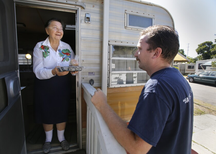 VISTA, CA: June 15, 2017 | Anne Stillman, 70, receives a meal from Meals on Wheels courier Christopher Topp on June 15, 2017. Topp was one of the first Meals on Wheels workers to use a new smartphone app to regularly report changes in client status as part of a pilot program now being expanded to Meals on Wheels centers across the nation.