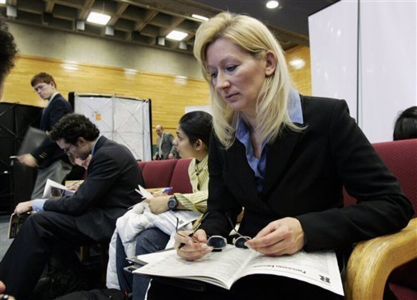 In this Jan. 7, 2009 file photo, Janet Wos, 43, of Sayerville, N.J., sits with others as they look through a listing of all the employer booths at a job fair at Rutgers University on Wednesday, Jan. 7, 2009, in New Brunswick, N.J. New claims for jobless benefits increased more than expected last