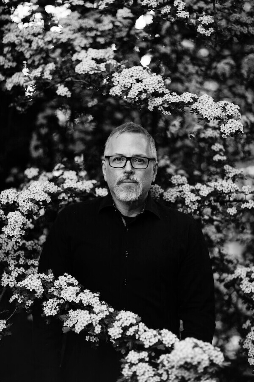 Portrait of a man standing among flowers