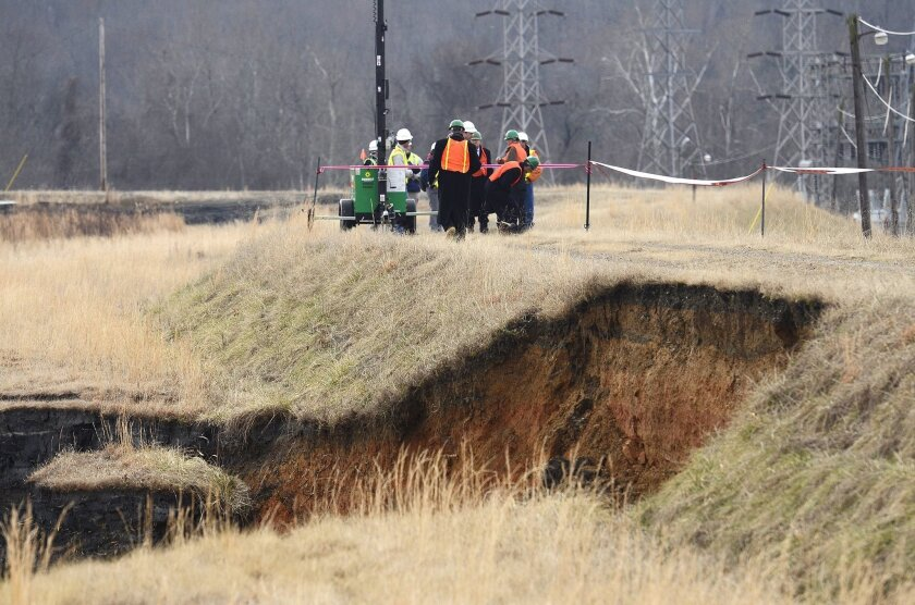 Officials examine the damage overlooking where a storm water pipe broke and coal ash was released into the Dan River in Eden, N.C.