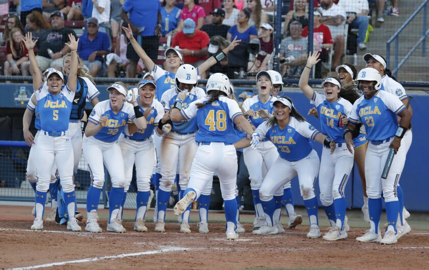 The UCLA softball team celebrates a home run against Oklahoma in the Women's College World Series in June.