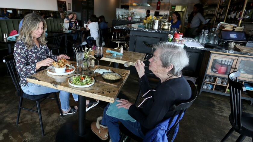 The New Deal owner Kerry Krull, left, enjoys a fried chicken sandwich while her mother has the Mac &