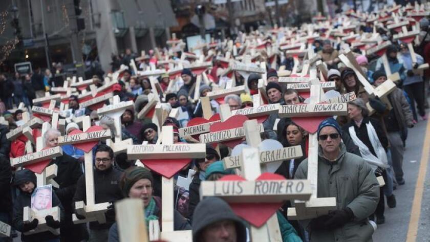 Residentes, activistas, amigos y familiares de víctimas de violencia armada marcharon en Chicago el 31 de diciembre de 2016, llevando cerca de 800 cruces de madera con los nombres de los fallecidos en la ciudad durante ese año.