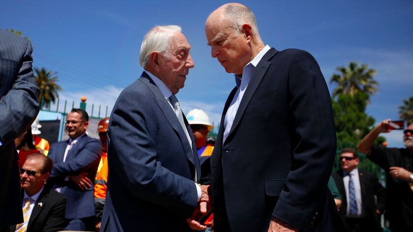 California Transportation Commission member Joseph Tavaglione, left, greets Gov. Jerry Brown before a news conference in Riverside on April 4 on the proposed gas tax for road repairs.